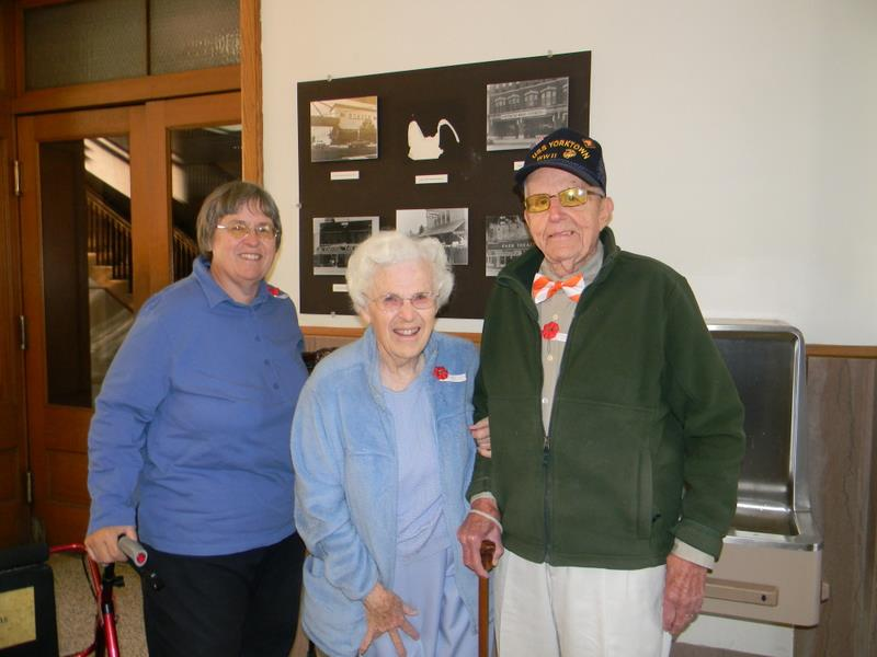 Two women in blue stand with man in green with WWII veteran hat on, in hallway of Court house
